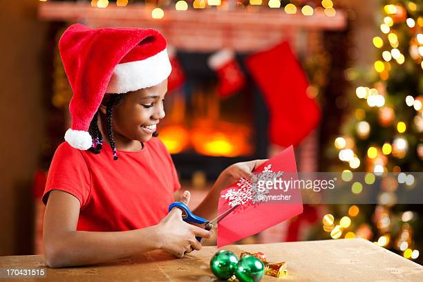 Beautiful girl making Christmas cards.