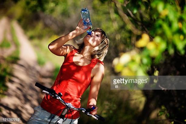 Linda Menina em uma bicicleta água de bebida