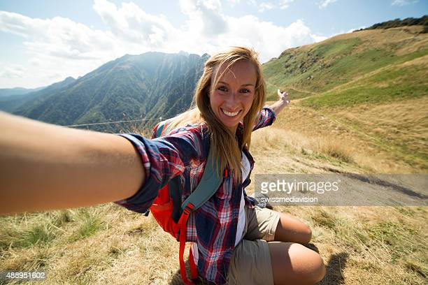 Beautiful girl on hiking trail taking selfie