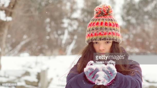 Beautiful girl outdoors holding a pile of snow at an open field