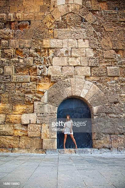 Beautiful girl posing next to an old building in Tarragona