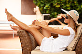 Beautiful girl relaxing on a resort wearing a straw hat