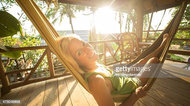 Beautiful girl relaxing on hammock at sunset