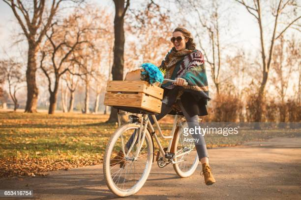 Beautiful girl riding bicycle in the park on the autumn day.