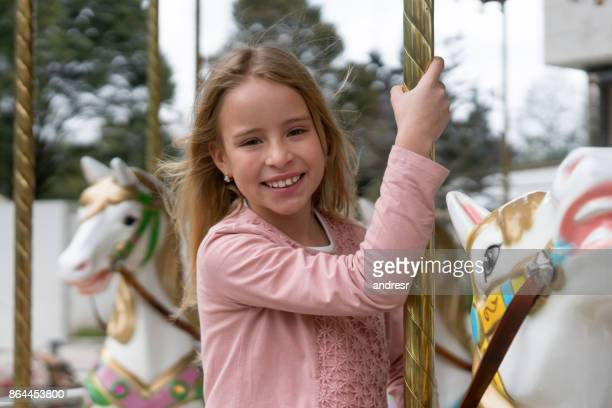 Beautiful girl riding on the carrousel at a traveling carnival