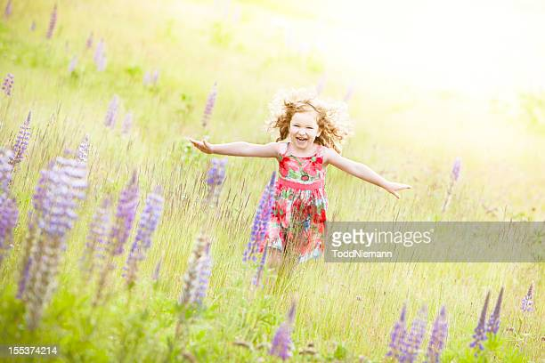 Beautiful girl running through field with flower.