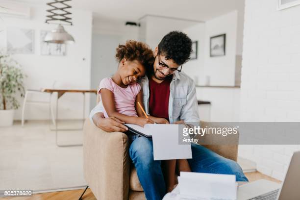 Beautiful girl sits at his father's lap and draws