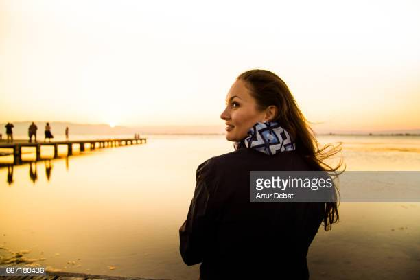 Beautiful girl sitting and contemplating the sunset over the Ebro Delta in the Mediterranean sea from wood pier and stunning sunlight during a weekend travel in the region.