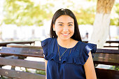 Close up portrait of cute teenage girl sitting outdoors on park bench and smiling