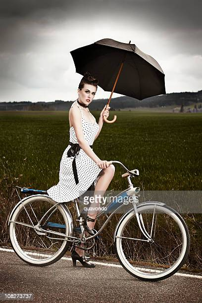 Beautiful Young Woman on Antique Bike Holding Umbrella, Copy Space
