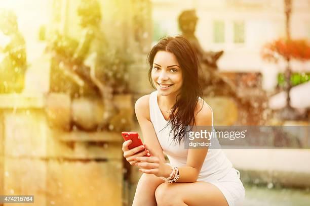 Schöne Mädchen lächelnd und spielt mit smartphone