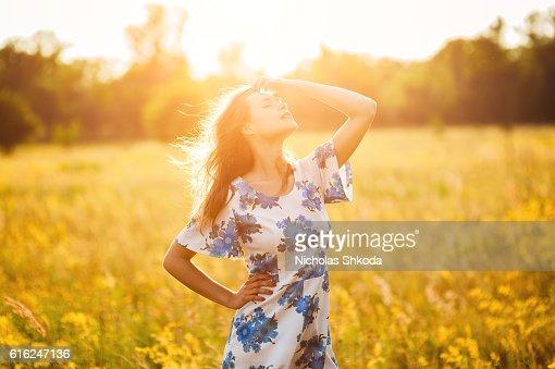 Beautiful girl the flowers field woman the flowers field sunset : Stock Photo