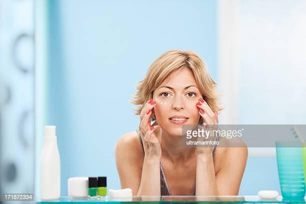 Belle femme à l'aide de la crème pour le visage