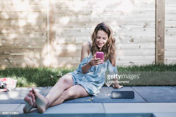 A beautiful girl using her cellphone near a swimming pool