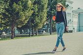 A beautiful girl walks down the street with coffee.