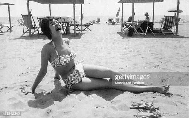 'A beautiful girl wearing a fashionable white patterned bikini lying on the thin sand of the wellknown beach resort of Tuscany she laughs happily...