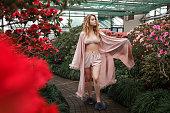 Beautiful girl wearing pink bathrobe and lingerie standing in flower garden. Horizontal full lenght portrait.