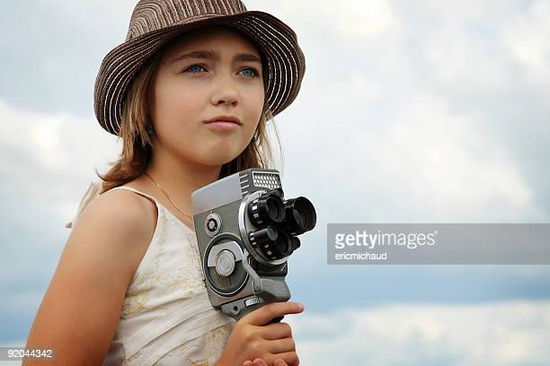 Beautiful girl with a vintage video camera