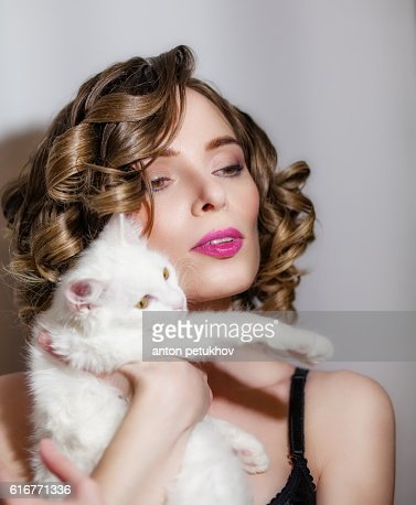 Beautiful girl with a white fluffy cat in her arms. : Stock Photo