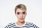 beautiful girl with short hair, dressed in a striped sweater with an unusual make-up posing in studio