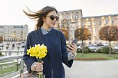 Beautiful girl with bouquet of yellow spring flowers, young woman reading text with smartphone, background city architecture, golden hour.