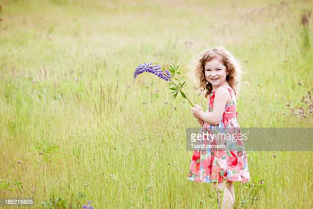 Beautiful girl with flower smiling in field.