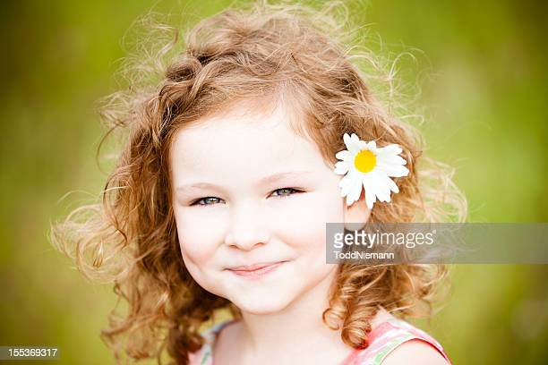 Beautiful girl with flower standing in field.