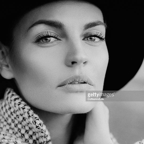 Beautiful girl with make-up, dressed in old-fashioned coat and hat