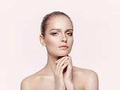 Close up beauty portrait of young model with nude professional makeup. Not isolated, light pink background.