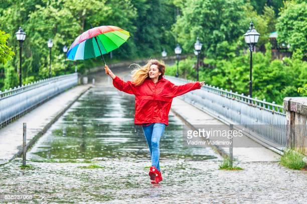 Beautiful girl with umbrella dancing in the rain