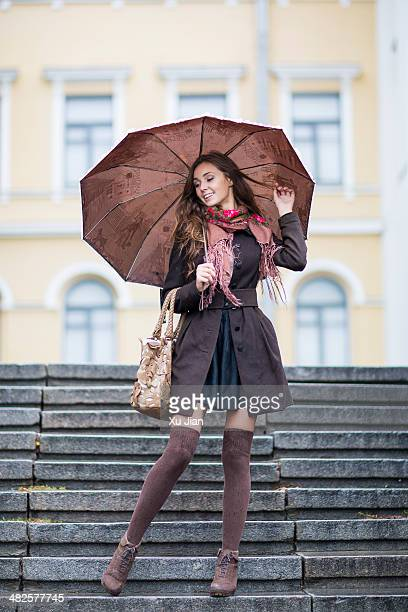 Beautiful girl with umbrella in rain