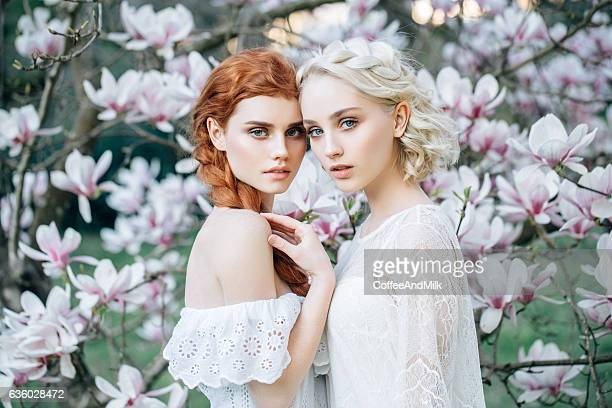 Beautiful girls on the background of spring bush