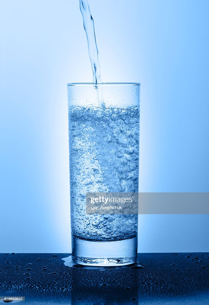 Beautiful glass with water on a blue background : Stock Photo