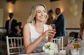 Young woman is sitting at a table at a wedding with a glass of champagne.