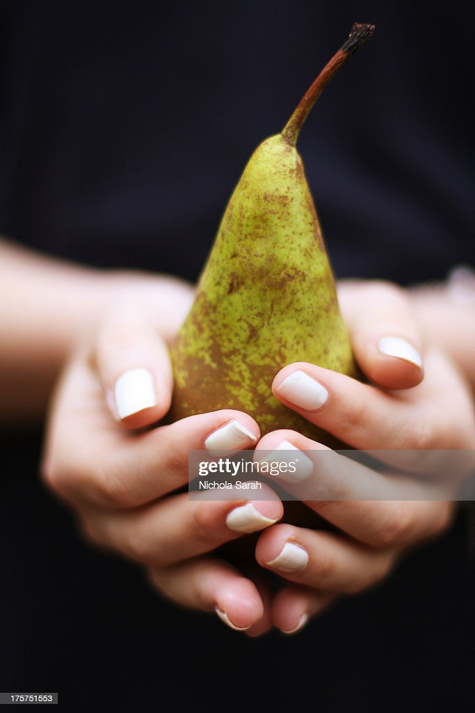 Beautiful hands holding a pear : Stock Photo