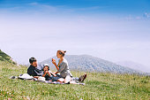 Beautiful happy family spends time on nature in the mountains. Family background. Lifestyle, Travel concept. Parent and child together. Velika Planina or Big Pasture Plateau in the Kamnik Alps, Sloven