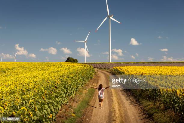 Beautiful happy girl enjoying time on the road in the middle of sunflowers landscape, with wind power and sky with white clouds on background
