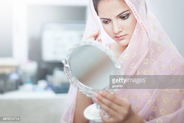 Beautiful, happy Hindu woman looking her face in a mirror.
