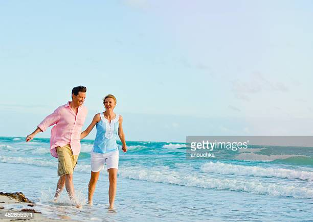 Beautiful Happy Mature Couple Having fun on the beach