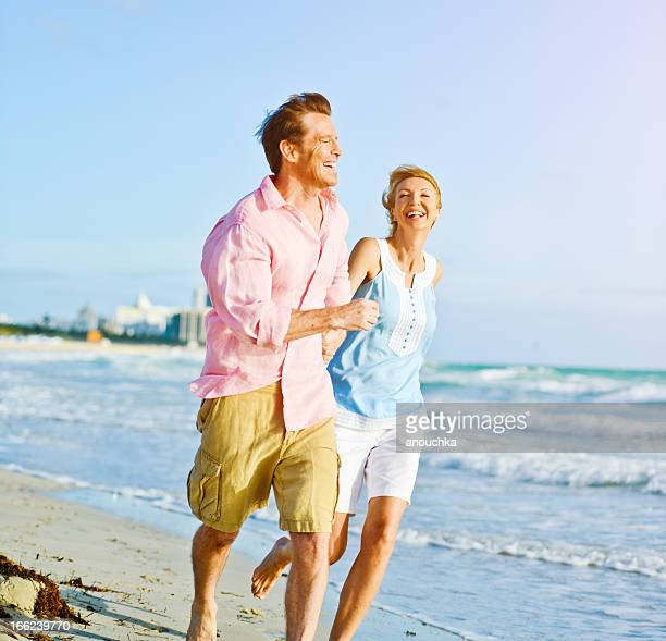 Beautiful Happy Mature Couple Running on the beach