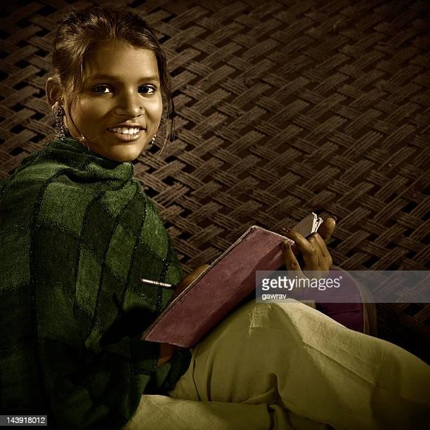 Schöne glücklich, ländlichen indische Mädchen hält ein Notizbuch und Stift