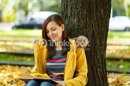 Una Feliz Sonriente Pelo Castaño Mujer Bella Capa Amarilla Y Los Pantalones  Vaqueros Sentados Debajo Del árbol De Arce Con Un Libro Rojo En El Parque  De La ... 5fca9daa143b
