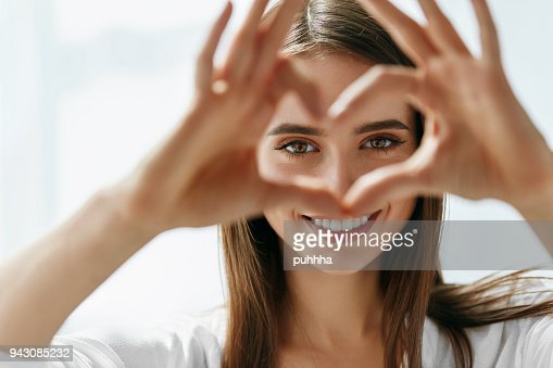 Beautiful Happy Woman Showing Love Sign Near Eyes. : Foto stock