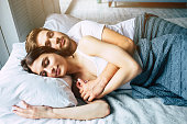 Beautiful happy young couple sleeping in bed in the morning and hugging. Love and relationships concept