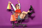 beautiful happy young woman in sunglasses holding paper bags and sitting in shopping trolley on violet
