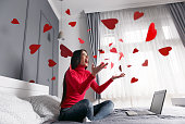 Beautiful, happy, young woman throwing red heart-shapes in the air, sitting on the bed