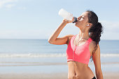 Beautiful healthy woman with earphones drinking water on beach