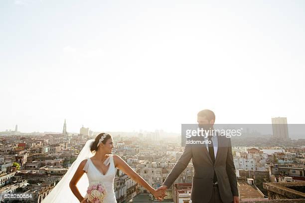 Hispanique beau couple tenant mains sur le toit