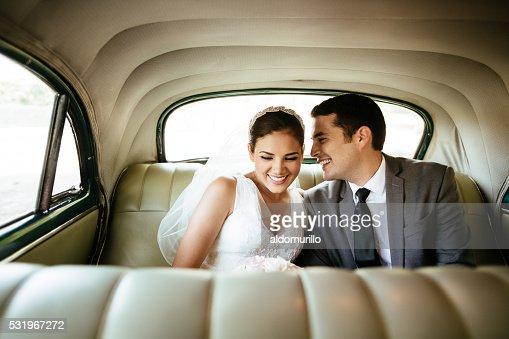 Beautiful Hispanic newlyweds laughing in backseat