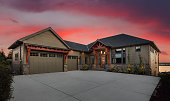 Beautiful Luxury Home Exterior at Sunset with Colorful Sky